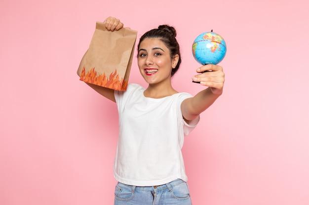 Вид спереди молодая женщина в белой футболке и синих джинсах позирует с улыбкой, держа маленький глобус и пакет с едой
