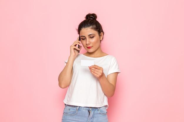 Вид спереди молодая самка в белой футболке и синих джинсах разговаривает по телефону