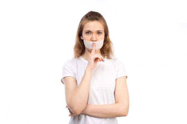 Вид спереди молодая самка в белой футболке с белой повязкой вокруг рта, показывая знак остановки говорить на белом