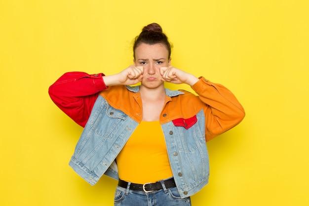 黄色いシャツのカラフルなジャケットとブルージーンズのposinと偽の泣き声の正面の若い女性