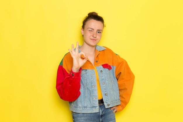 Вид спереди молодая женщина в желтой рубашке красочной куртке и синих джинсах позирует