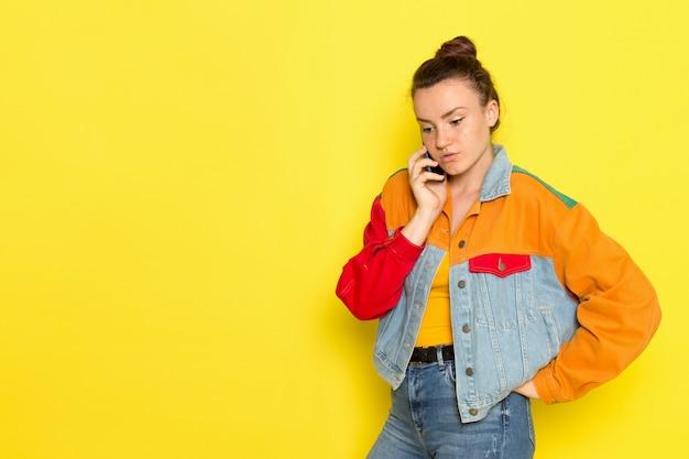 Вид спереди молодая самка в желтой рубашке красочной куртке и синих джинсах разговаривает по телефону