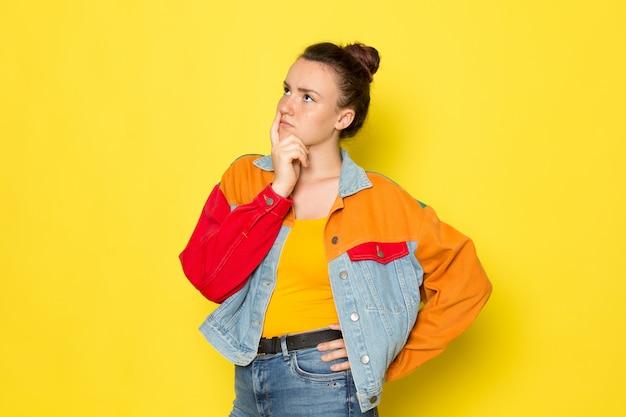 黄色のシャツのカラフルなジャケットとブルージーンズの思考の表情で正面の若い女性