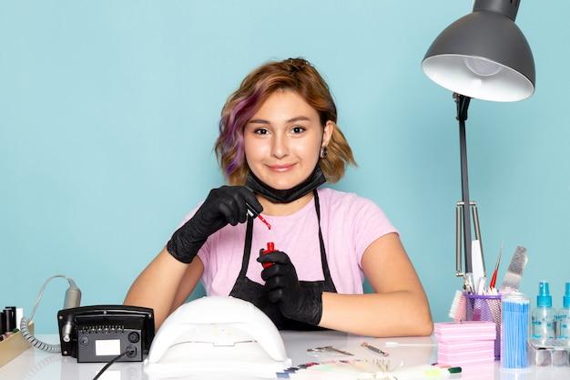 Вид спереди молодой женский маникюр в розовой футболке и черной накидке с черными перчатками, готовящаяся к своей работе на синем