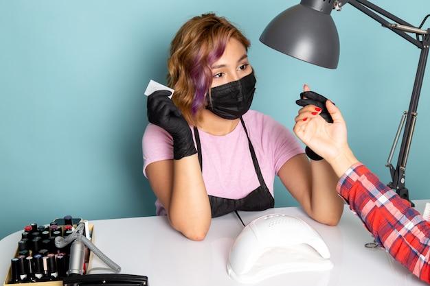 黒い手袋と青のマニキュアをしている黒いマスクのピンクのtシャツで正面の若い女性のマニキュア