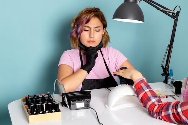 黒の手袋と青の迷った表情でマニキュアをしている黒いマスクとピンクのtシャツで正面の若い女性のマニキュア