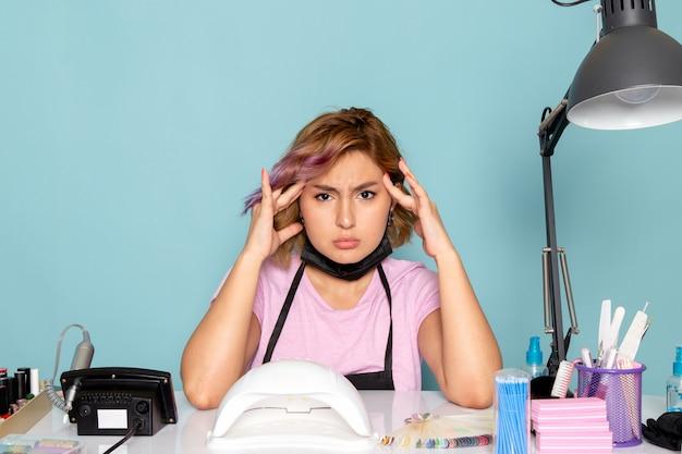 黒の手袋と青に頭痛を持つ黒のマスクとピンクのtシャツで正面の若い女性のマニキュア