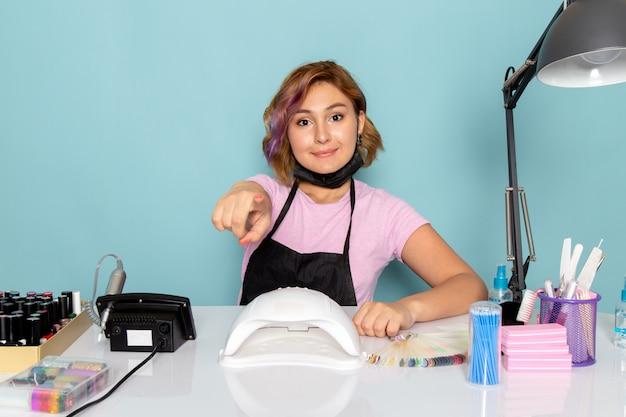 正面図の若い女性のマニキュア、ピンクのtシャツ、黒い手袋、テーブルの前に座っていると笑顔の青いマスク