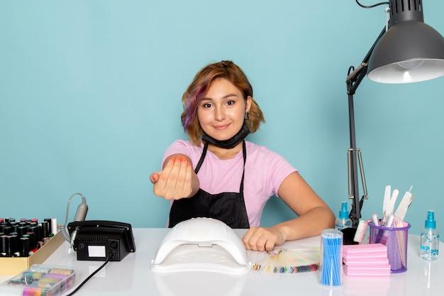 黒の手袋とテーブルの前に座っていると、笑みを浮かべて青の黒いマスクとピンクのtシャツの正面の若い女性のマニキュア