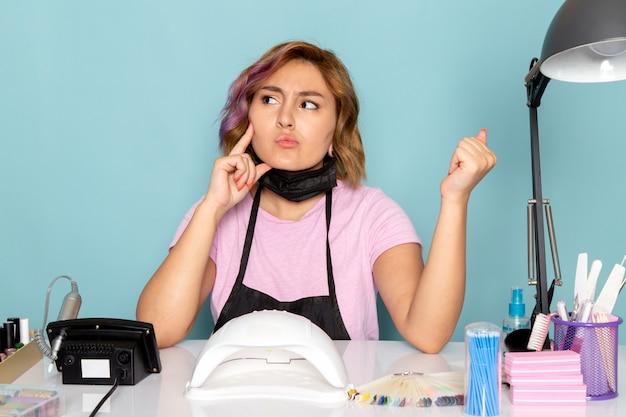 黒の手袋とテーブルの前に座っていると青を考えて黒いマスクとピンクのtシャツで正面の若い女性のマニキュア