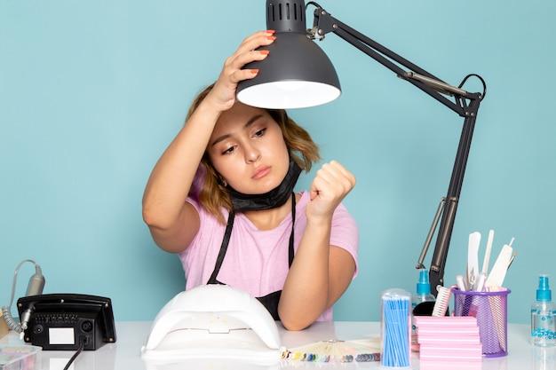 黒の手袋と青のテーブルの前に座っている黒いマスクとピンクのtシャツで正面の若い女性のマニキュア