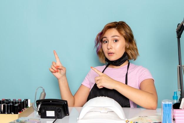 黒の手袋と青で指摘されているテーブルの前に座っている黒いマスクとピンクのtシャツで正面の若い女性のマニキュア