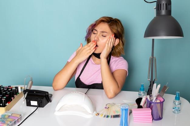Вид спереди молодой женский маникюр в розовой футболке с черными перчатками и черной маской сидит перед столом и чихает на синем