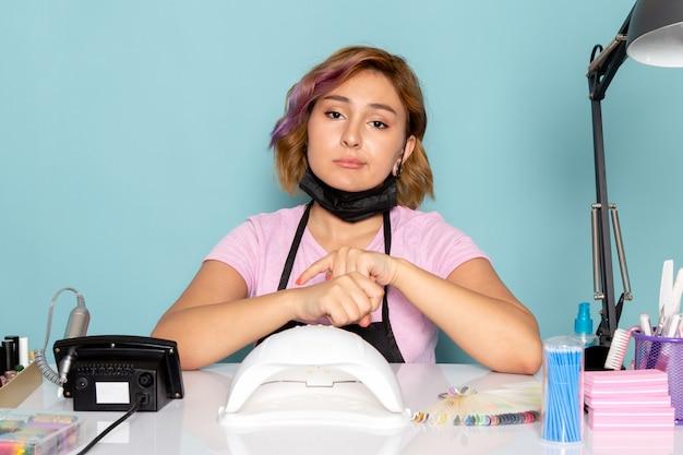 黒い手袋と青の退屈な表情でテーブルの前に座っている黒いマスクとピンクのtシャツで正面の若い女性のマニキュア