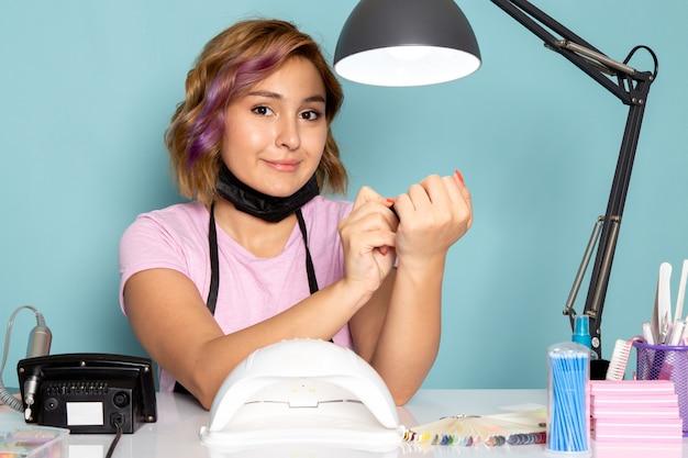 正面図の若い女性のマニキュアピンクのtシャツに黒い手袋とテーブルの上に座っている黒いマスクとブルーのネイル