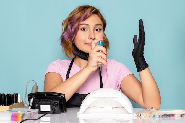 黒い手袋とブルーにスプレーを使用して黒いマスクのピンクのtシャツで正面の若い女性のマニキュア