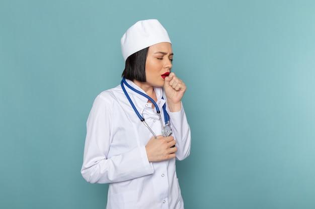 Вид спереди молодая медсестра в белом медицинском костюме и синий стетоскоп кашель