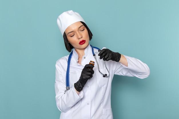 Вид спереди молодая медсестра в белом медицинском костюме и синем стетоскопе с таблетками на синем столе врача больницы