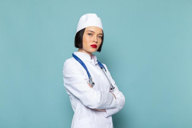 Вид спереди молодая медсестра в белом медицинском костюме и синем стетоскопе позирует на синем столе врача больницы