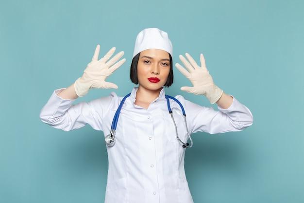 白い医療スーツと青い聴診器の正面の若い女性看護師は青い机の医学病院の医師に彼女の手を示しています