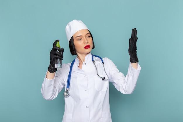 Вид спереди молодая медсестра в белом медицинском костюме и синем стетоскопе, распыляющая руки на синий стол врача больницы