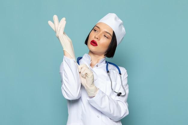 Вид спереди молодая медсестра в белом медицинском костюме и синем стетоскопе в белых перчатках на синем столе врача больницы