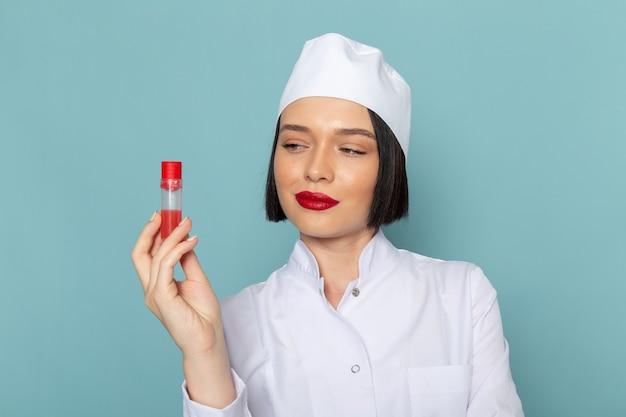 Вид спереди молодая медсестра в белом медицинском костюме, держащая флягу на синем столе врача больницы