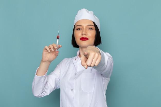 Вид спереди молодая медсестра в белом медицинском костюме с инъекцией на синем столе врача больницы