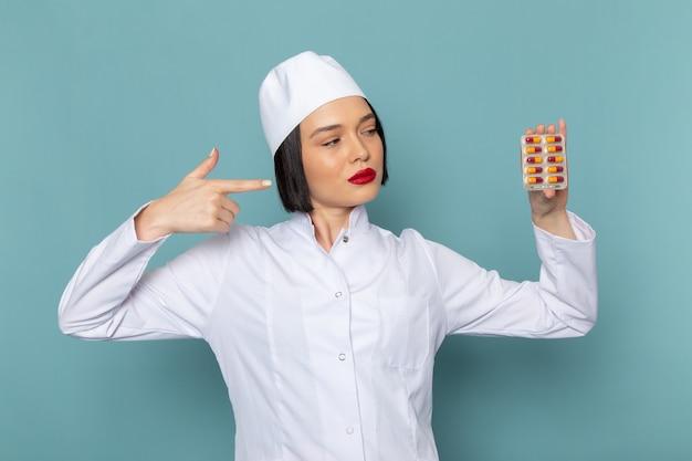 Вид спереди молодая медсестра в белом медицинском костюме с таблетками на синем столе врача больницы