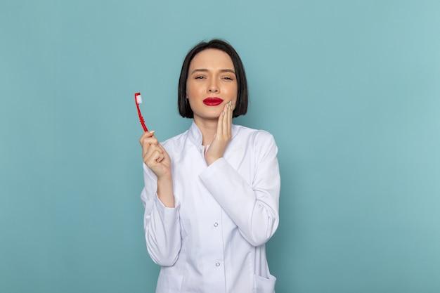 青い机の医学病院の医師に歯ブラシを保持している白い医療スーツの正面の若い女性看護師