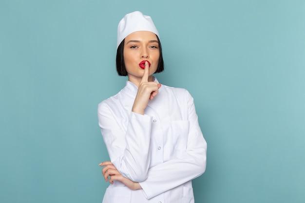 Вид спереди молодая медсестра в белом медицинском костюме позирует и показывает знак тишины на синем столе врача больницы
