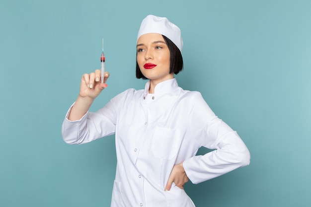 Вид спереди молодая медсестра в белом медицинском костюме готовит инъекцию на синем столе врача больницы