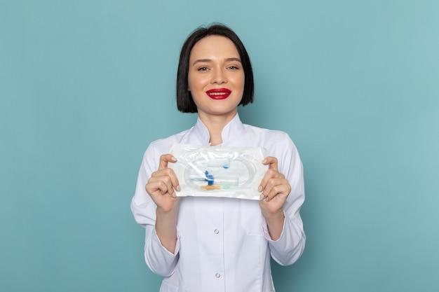 Вид спереди молодая медсестра в белом медицинском костюме, улыбаясь, держа пакет на синем столе врача больницы