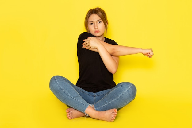 Молодая женщина, сидящая в черной рубашке и синих джинсах, позирует с болью из-за повреждения руки на желтом