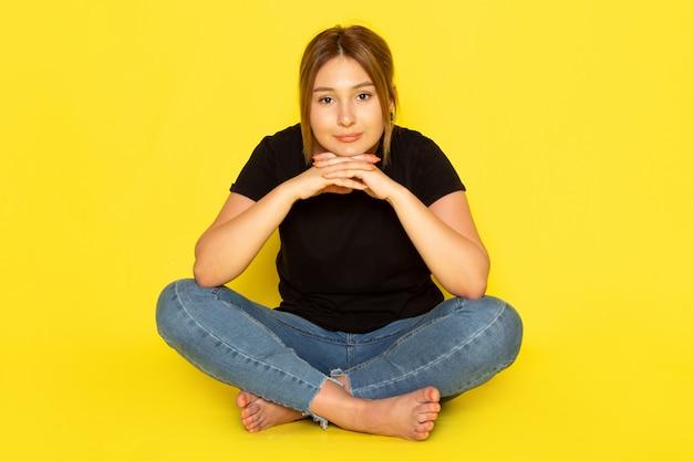 Вид спереди молодая женщина, сидящая в черной рубашке и синих джинсах, позирует с улыбкой на желтом