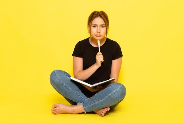 黒のシャツとブルージーンズに座ってメモを書き、黄色の背景の女性の色の美しさを考える正面の若い女性