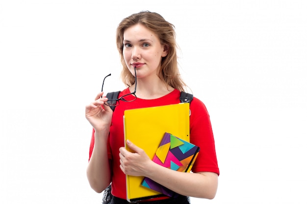 Вид спереди молодая студентка в красной рубашке черная сумка, держащая тетради, улыбаясь на белом