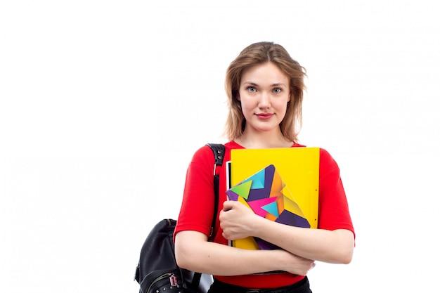 Вид спереди молодая студентка в красной рубашке черной сумке, холдинг тетрадей, улыбаясь на белом
