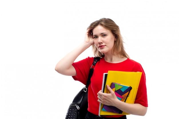 Вид спереди молодая студентка в красной рубашке черная сумка, держа ручку и тетради на белом