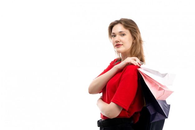 빨간 셔츠 검은 가방에 전면보기 젊은 여성 학생 흰색에 쇼핑 패키지를 들고 웃