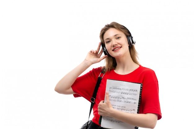 Вид спереди молодая студентка в красной рубашке черная сумка с черными наушниками, слушая музыку, улыбаясь, держа тетрадь на белом