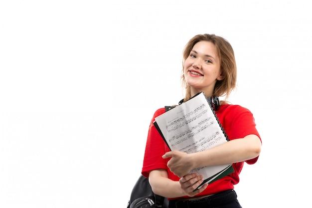 흰색에 카피 북을 들고 웃 고 검은 이어폰 빨간 셔츠 검은 가방에 전면보기 젊은 여성 학생