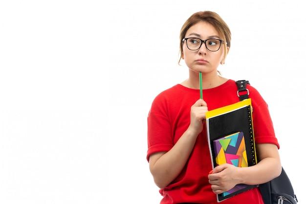 Вид спереди молодая студентка в красной футболке черные джинсы держит различные тетради и файлы, держа карандаш мышления на белом