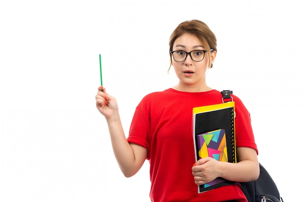 Вид спереди молодая студентка в красной футболке черные джинсы держит различные тетради и файлы, держа карандаш с сумкой на белом