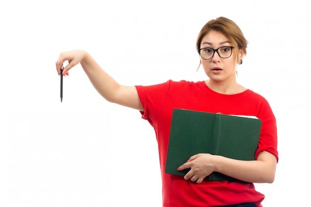 Вид спереди молодая студентка в красной футболке держит зеленую тетрадь на белом