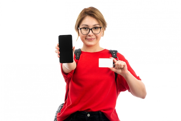 Вид спереди молодая студентка в красной футболке в черной сумке держит черный смартфон и белую карточку, улыбаясь на белом