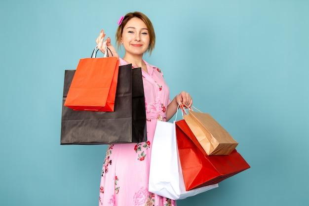 Вид спереди юная леди в цветочном дизайне розового платья держит пакеты с покупками и улыбается на синем