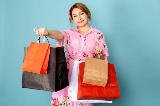 花の正面の若い女性は、ショッピングパッケージを保持し、青に笑みを浮かべてピンクのドレスを設計