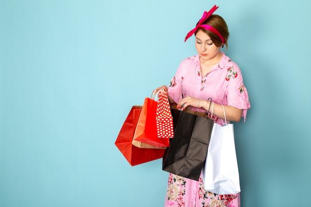 Вид спереди юная леди в розовом платье с цветочным дизайном, держащая пакеты с покупками на синем