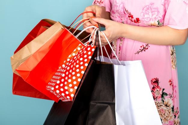 花の正面の若い女性はピンクのドレスを保持しているブルーのショッピングパッケージを保持しているポーズを設計